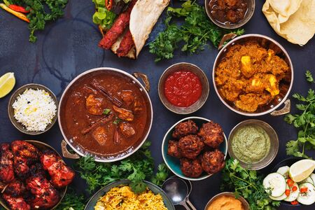 Taste of India. A selection of Indian food with various bowls of food featuring chicken tikka masala, rogan josh, kebabs, tandoori chicken wings, pasties, poppadoms with dips and naan bread