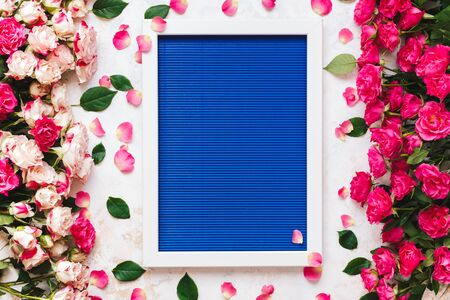 Beautiful pink and red roses directed at each other on rustic white surface and empty white wooden frame on blue texture. Top view, blank space