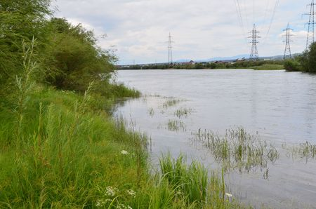This picture shows a riverside with high-voltage power line columns on the background Stockfoto - 109404657