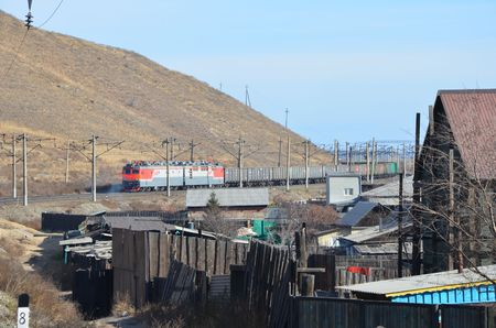 This picture shows a train coming with a house on foreground Redactioneel