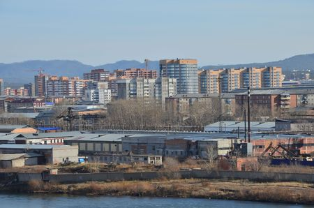 This picture shows riverside warehouses with buildings on background