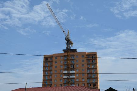This picture shows a crane in front of a building Stockfoto