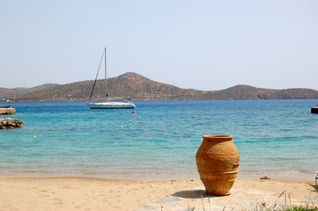 Beach  with yacht and amphora view, Crete, Greece (focus is on the amphora) photo