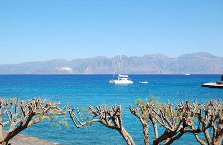 Luxury yacht, turquoise Aegean Sea and cut trees, Crete, Greece photo
