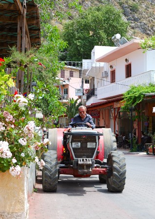 SPILI, CRETE - MAY 16: Busy Greek farmer drives his tractor through the Spili village on May 16, 2010 in Spili village, Crete, Greece. At the continental Greece were performed strikes against salaries reduction