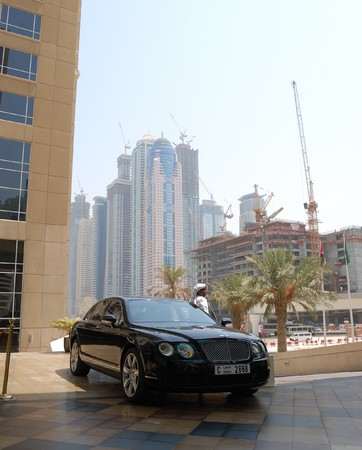 DUBAI, UAE - AUGUST 27: Arabic businessman near his Bently  limousine and skyscrapers construction at background. In Dubai civil works conducts 24 hours every day on August 27, 2009 in Dubai, United Arab Emirates