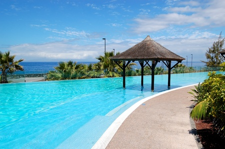 Swimming pool with Bali type hut and beach of luxury hotel, Tenerife island, Spain
