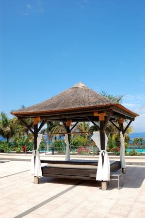 Bali type hut near beach and swimming pool, Tenerife island, Spain Stock Photo - 10053476