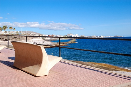 Seafront and bench at Playa de las Americas, Tenerife island, Spain photo