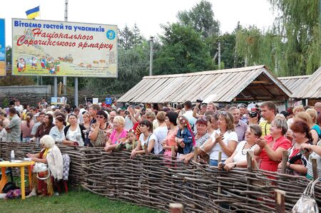 well known: VELIKI  SOROCHINTSI VILLAGE, POLTAVA REGION, UKRAINE - AUGUST 20: Crowd of people watching perfomance of the traditional Ukrainian folk group at the open-air famous National Sorochintsi Fair on August 20, 2011. The Sorochintsi Fair is the most well known  Editorial