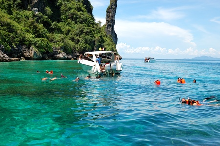 KOH PHI PHI, THAILAND - SEPTEMBER 13: Snorkeling tourists on turquoise water of Maya Bay lagoon on September 13, 2010 in Koh Phi Phi island, Thailand. Maya Bay is the major travel destionation in Thailand