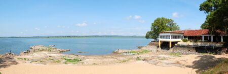 The panorama of beach at lake and restaurant with outdoor terrace and lake view, Sri Lanka