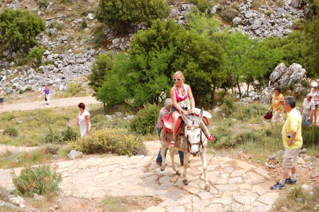 CRETE ISLAND, GREECE - MAY 13: The female tourist on a donkey and local Greek man controls the animal on the way to the Cave of Zeus on May 13, 2010 in Crete, Greece.  15000000 tourists have visited Greece in year 2010