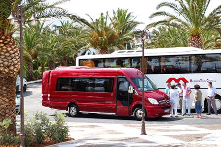 Creta, Grecia - 13 maggio: Il bus moderni per il trasporto turisti e un gruppo di turisti sono vicino all'albergo il 13 maggio 2010 a Creta, Grecia. 15000000 di turisti hanno visitato la Grecia per l'anno 2010 Editoriali