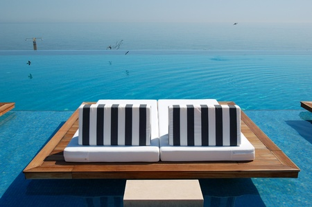 greece shoreline: Infinity swimming pool by beach at the modern luxury hotel, Pieria, Greece Stock Photo