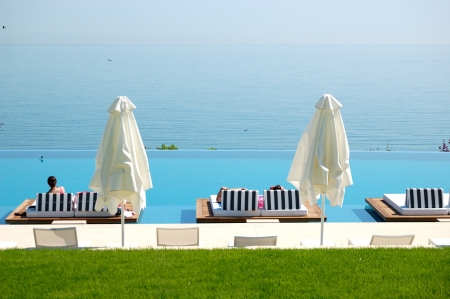aegean sea: Infinity swimming pool by beach at the modern luxury hotel, Pieria, Greece Editorial