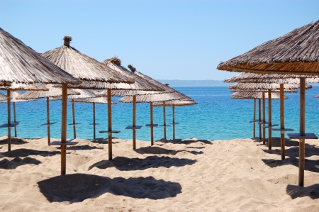 greece shoreline: Umbrellas on a beach and turquoise water at the luxury hotel, Halkidiki, Greece Stock Photo