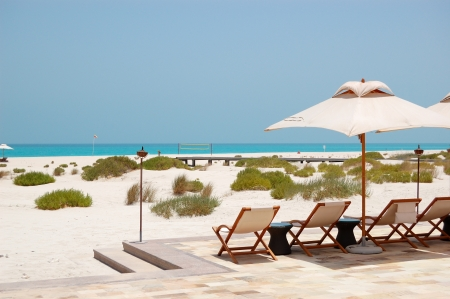 sunbeds: Sunbeds and umbrellas at the beach of luxury hotel, Abu Dhabi, UAE