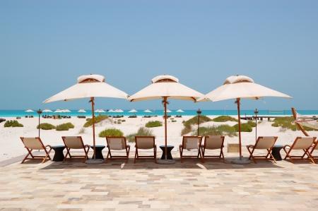 Sunbeds and umbrellas at the Beach of luxury hotel, Abu Dhabi, UAE photo