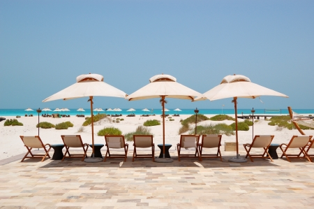 hut: Sunbeds and umbrellas at the Beach of luxury hotel, Abu Dhabi, UAE Stock Photo