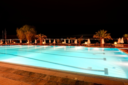 Swimming pool near beach in night illumination at the luxury hotel, Peloponnes, Greece photo