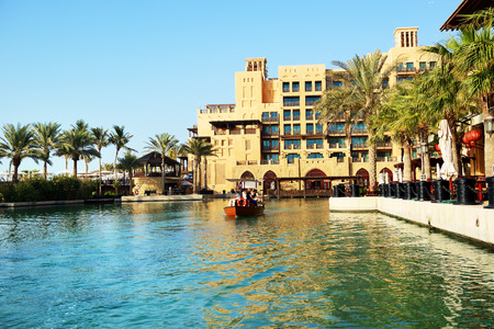 DUBAI, UAE - SEPTEMBER 9: View of the Souk Madinat Jumeirah and tourists swimming on abra boat. Madinat Jumeirah encompasses two hotels and clusters of 29 traditional Arabic houses on September 9, 2013 in Dubai, UAE