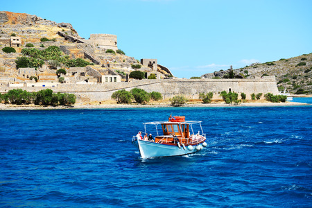 expected: SPINALONGA, GREECE - MAY 14: The motor yachts with tourists are near Spinalonga island on May 14, 2014 in Spinalonga, Greece. Up to 16 mln tourists is expected to visit Greece in year 2014.