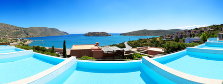 Panorama of swimming pools at luxury hotel with a view on Spinalonga Island, Crete, Greece