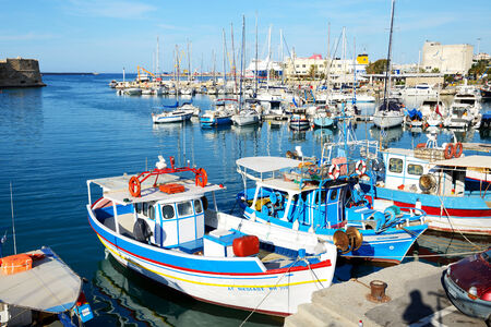 expected: HERAKLION, GREECE - MAY 12: The traditional Greek fishing boat are near pier and tourists on May 12, 2014 in Heraklion, Greece. Up to 16 mln tourists is expected to visit Greece in year 2014.