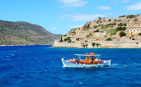 SPINALONGA, GREECE - MAY 14: The motor yacht with tourists is near Spinalonga island on May 14, 2014 in Spinalonga, Greece. Up to 16 mln tourists is expected to visit Greece in year 2014.
