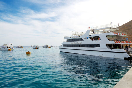 sharm: SHARM EL SHEIKH, EGYPT -  DECEMBER 4: The yacht with tourists is near pier in harbor of Sharm el Sheikh. Up to 12 million tourists have visited Egypt in year 2013.