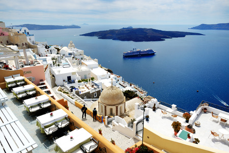 expected: FIRA, GREECE - MAY 17: The view on Fira town and tourists enjoying their vacation on May 17, 2014 in Fira, Greece. Up to 16 mln tourists is expected to visit Greece in year 2014. Editorial