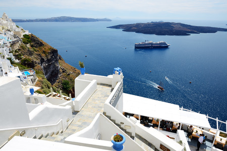 16 17: FIRA, GREECE - MAY 17: The view on Fira town and tourists enjoying their vacation on May 17, 2014 in Fira, Greece. Up to 16 mln tourists is expected to visit Greece in year 2014. Editorial