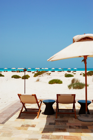 Sunbeds and umbrellas at the beach of luxury hotel, Abu Dhabi, UAE