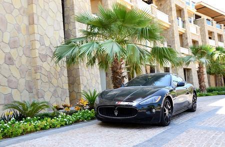 9 11: DUBAI, UAE - SEPTEMBER 9: The luxury Maserati Granturismo car is near luxurious hotel on September 9, 2013 in Dubai, United Arab Emirates. Hotels in Dubai attracted over 11 million guests in 2013.