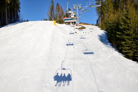 kids at the ski lift: The slope of Bukovel ski resort and shadow, Ukraine
