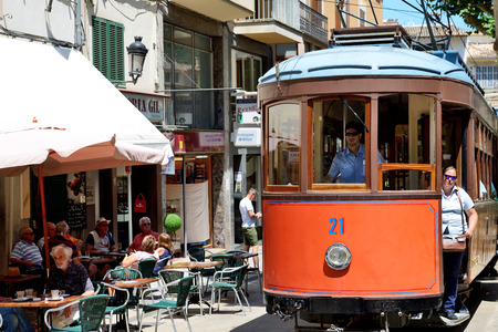 hollidays: MALLORCA, SPAIN - JUNE 2: The tram is on street of Soller town and tourists are in outdoor restaurant on June 2, 2015 in Mallorca, Spain. Up to 60 mln tourists is expected to visit Spain in year 2015. Editorial