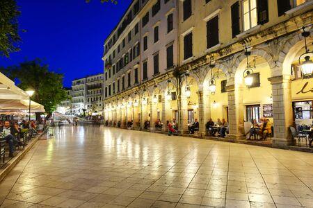 KERKYRA, GREEES - 14 de mayo: Los turistas están en cafés en Liston durante el atardecer el 14 de mayo, 2016, Kerkyra, Grecia. Se espera que hasta 16 millones de turistas para visitar Grecia en el año 2016. Editorial