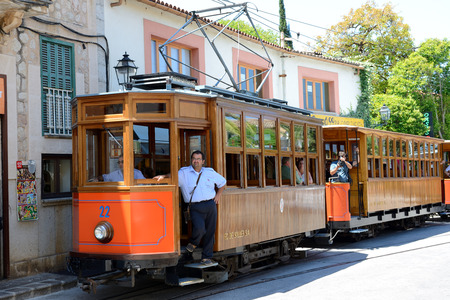 MALLORCA, SPAIN - JUNE 2: The tram is on street of Soller town and tourists are in outdoor restaurant on June 2, 2015 in Mallorca, Spain. Up to 60 mln tourists is expected to visit Spain in year 2015. Editorial