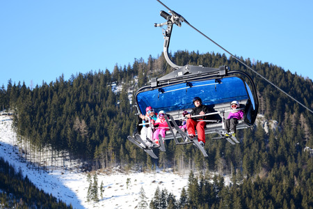 kids at the ski lift: JASNA, SLOVAKIA - JANUARY 22:  The cabins of Lucky cableway with family of skiers in Jasna Low Tatras. It is the largest ski resort in Slovakia with 49 km of pistes on January 22, 2017 in Jasna, Slovakia Editorial