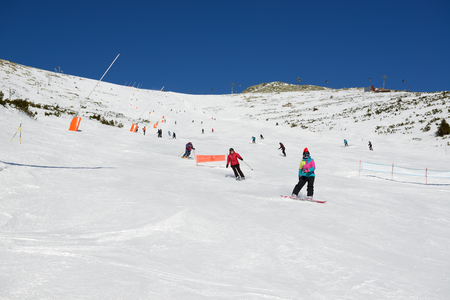 kids at the ski lift: JASNA, SLOVAKIA - JANUARY 23:  The skiers, snowborders and cableway in Jasna Low Tatras. It is the largest ski resort in Slovakia with 49 km of pistes on January 23, 2017 in Jasna, Slovakia