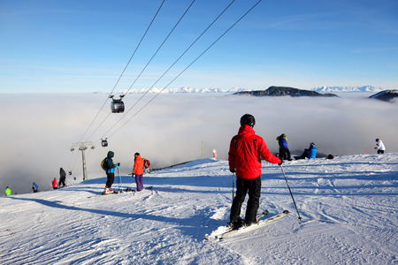 kids at the ski lift: JASNA, SLOVAKIA - JANUARY 25:  The skiers are on slope and fog in Jasna Low Tatras. It is the largest ski resort in Slovakia with 49 km of pistes on January 25, 2017 in Jasna, Slovakia Editorial