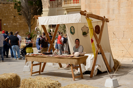 expected: MDINA, MALTA - APRIL 19: The women sells souvenirs at Mdina medieval festival and tourists on April 19, 2015 in Mdina, Malta. More then 1,6 mln tourists is expected to visit Malta in year 2015.