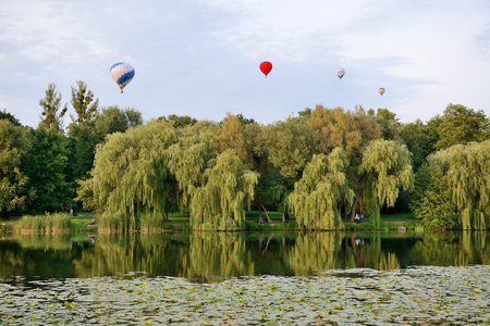 BILA TSERKVA, UKRAINE - AUGUST 25: The view on balloons are over  Olexandria Park and visitors on August 25, 2017 in Bila Tserkva, Ukraine. The balloons show is dedicated to Ukrainian Independence Day.