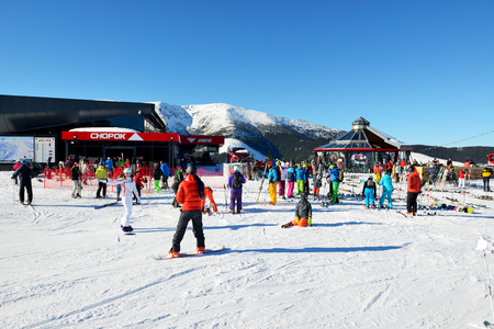 kids at the ski lift: JASNA, SLOVAKIA - JANUARY 22:  The skiers and Chopok cableway station in Jasna Low Tatras. It is the largest ski resort in Slovakia with 49 km of pistes on January 22, 2017 in Jasna, Slovakia