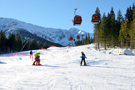 kids at the ski lift: JASNA, SLOVAKIA - JANUARY 22:  The snowpark, skiers and cableway in Jasna Low Tatras. It is the largest ski resort in Slovakia with 49 km of pistes on January 22, 2017 in Jasna, Slovakia