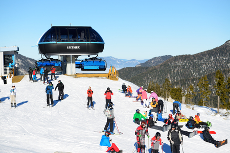 kids at the ski lift: JASNA, SLOVAKIA - JANUARY 23:  The skiers and cableway station in Jasna Low Tatras. It is the largest ski resort in Slovakia with 49 km of pistes on January 23, 2017 in Jasna, Slovakia Editorial