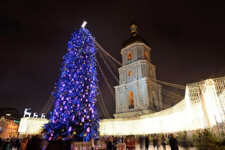 KYIV, UKRAINE - DECEMBER 28: The group of people and the Bell Tower of Saint Sofias Cathedral and New Year Tree at background on December 28, 2017 in Kyiv, Ukraine Editorial