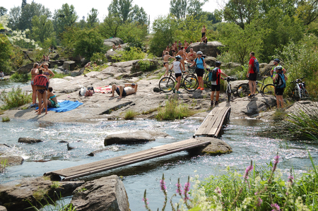 BOGUSLAV, UKRAINE - AUGUST 5: The group of cycklists and people enjoying their holiday are near Ros river on August 5, 2018 in Boguslav, Ukraine.