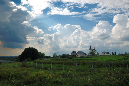The beam of light from the sky shines to orthodox church direction in Chaiky village, near Boguslav town, Ukraine Banco de Imagens